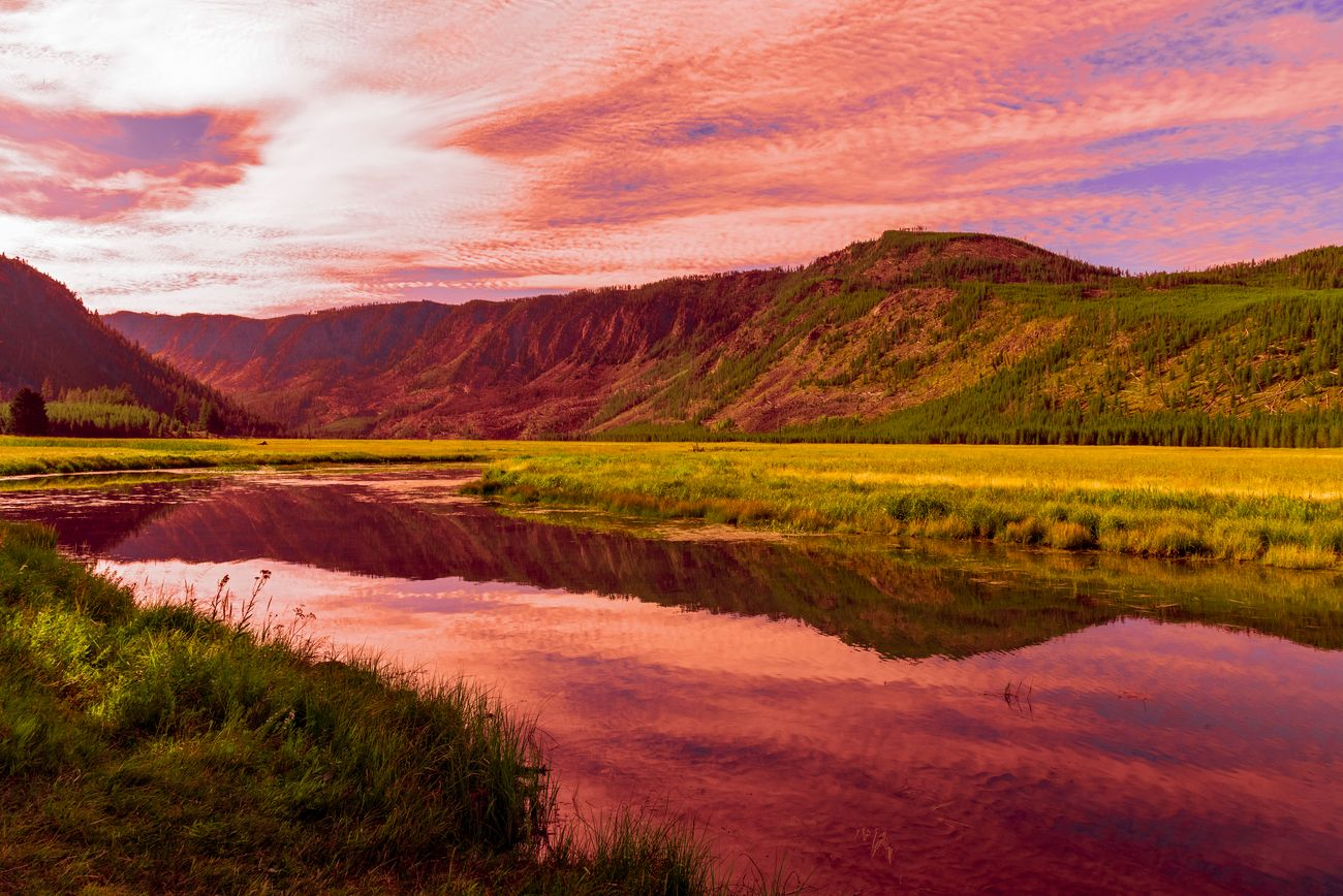 Sunset in Yellowstone National Park, Madison river. colorful orange and red sky reflected in the river.