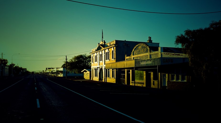 Small country town, old stores close but the signs remain, early morning light illuminates store ...