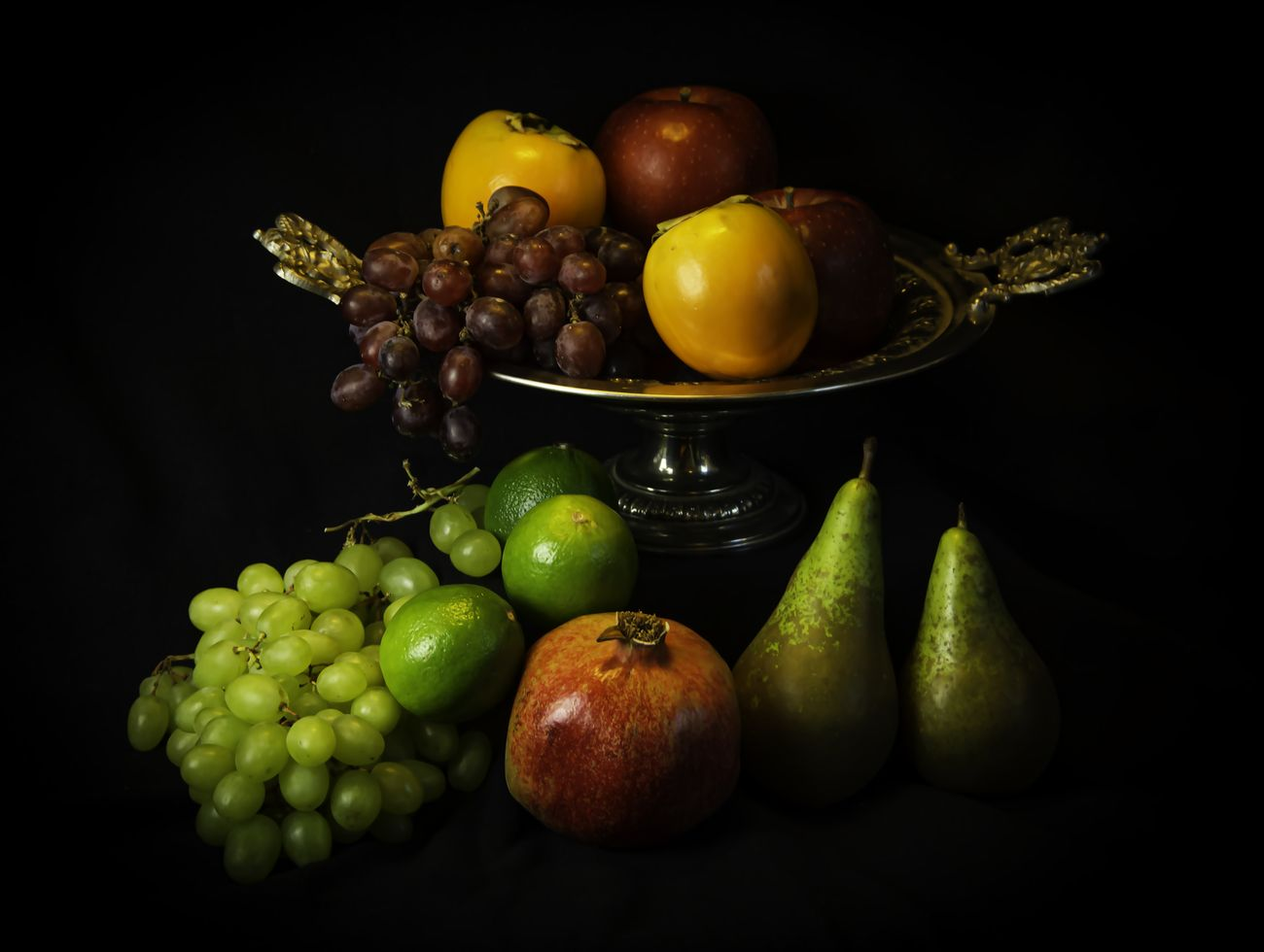 Still life with fruits and an antic bowl against a black background
