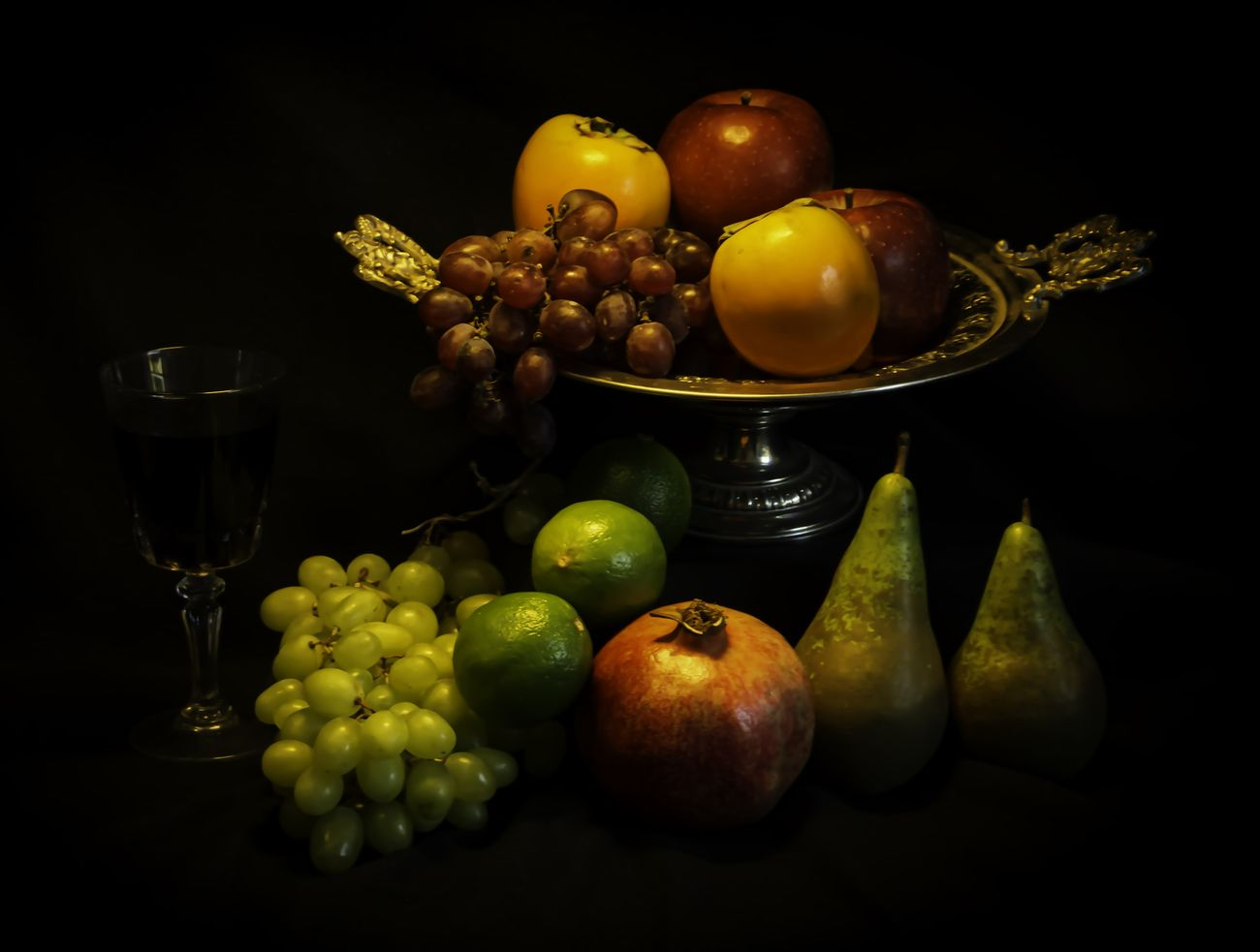 Still life with fruits in an antic bowl and a glass of red wine against black background