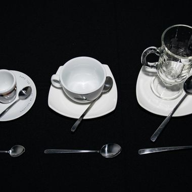 a selection of different shaped and sized coffee cups along side their spoons and plates