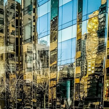 Street reflections on the glass side of a building. Image captured during a walk in New York City, USA.