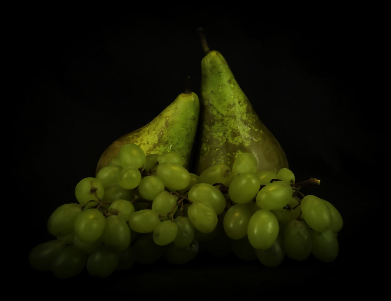 Still life pears and grapes against black