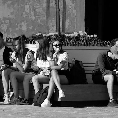 A study in group dynamics and human interaction - A group of young tourists rests in the shade in St. George's Square.