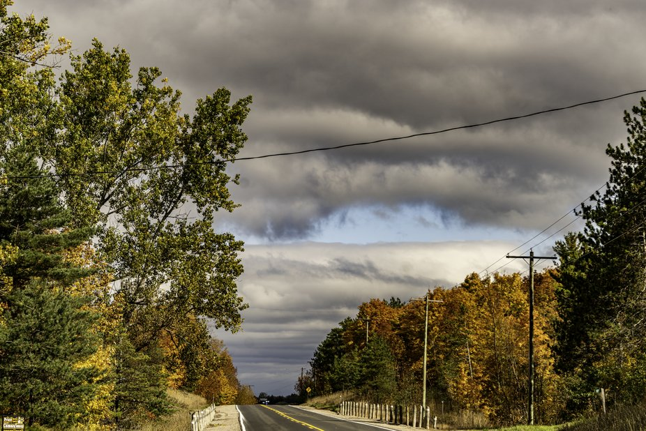 On a road trip to take photographs of the changing landscape in the fall stopped the vehicle to compose this shot of a highway in Autumn.
