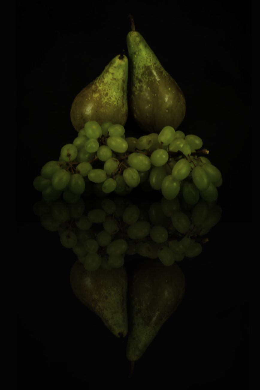 Still life of pears and grapes reflection on black