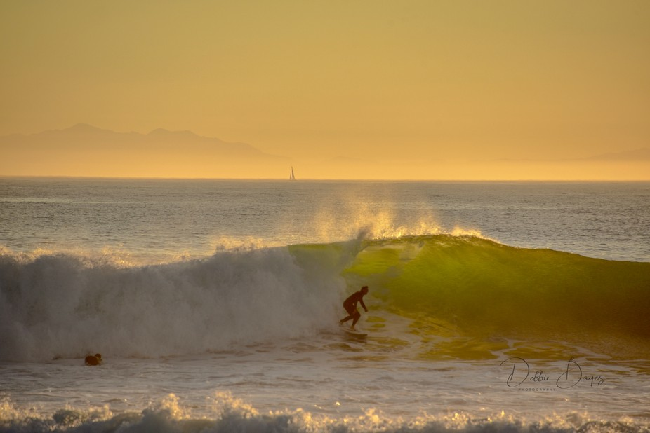 Surfing just that one more wave at the last light of day.