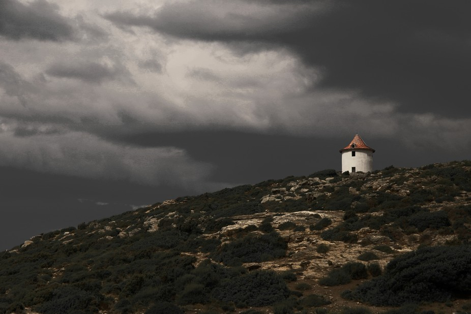 French Corsican ancient chapel with imposing clouds