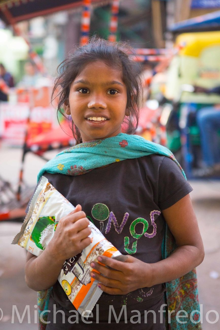 A young girl in the Bazaar in New Delhi India showing her gratitude after purchasing rice