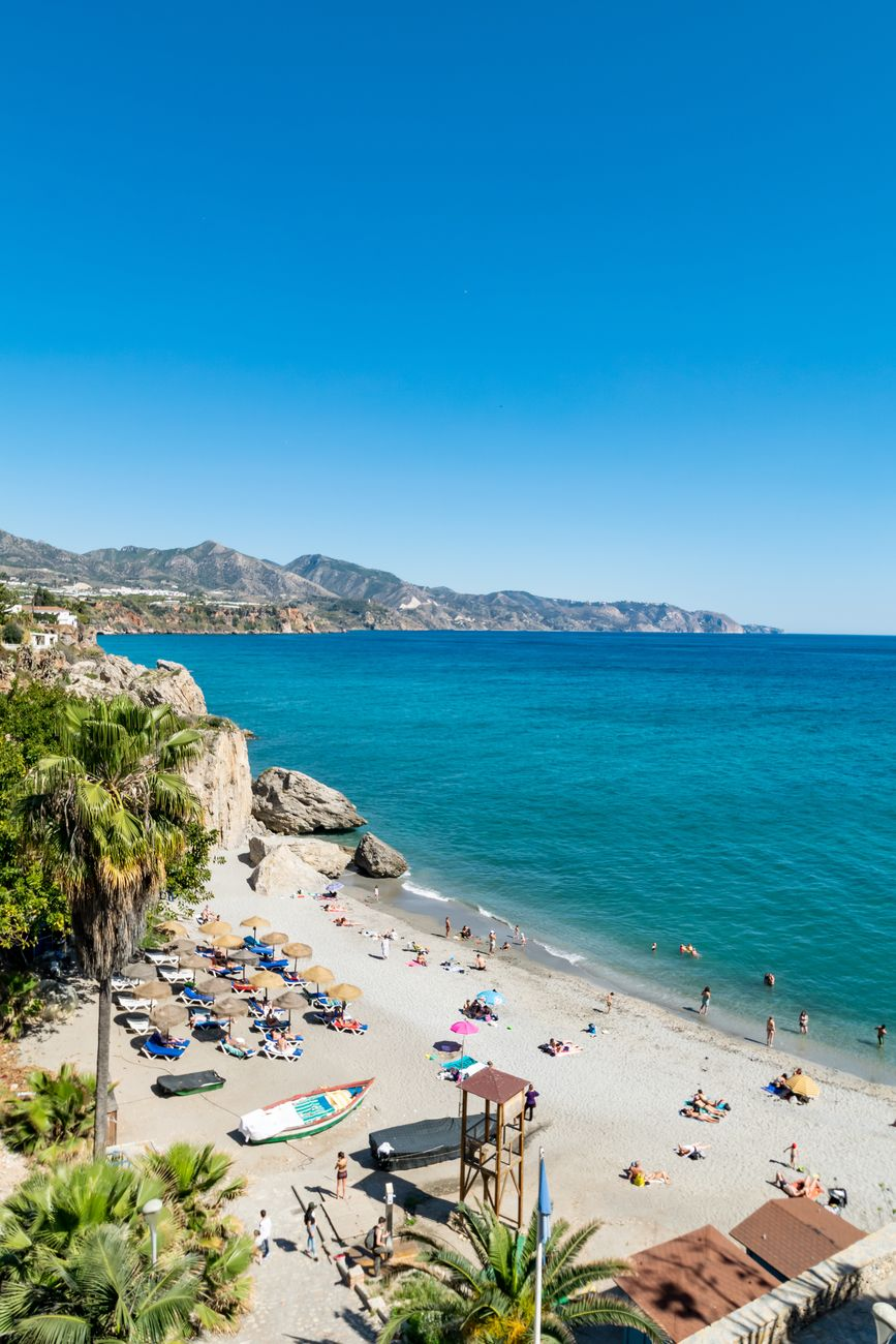 a summer beach scene taken from El Balcon de Europa overlooking one of the small beaches of Nerja, Spain