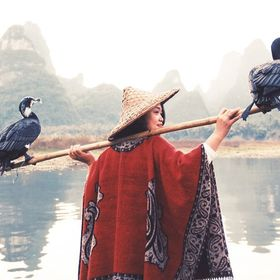 A friend of mine posing with the great cormorants on afterdeck with the picturesque Guilin karst mountain landscape in the background.