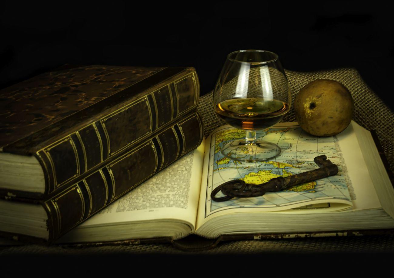 Still life books key cognac and pear