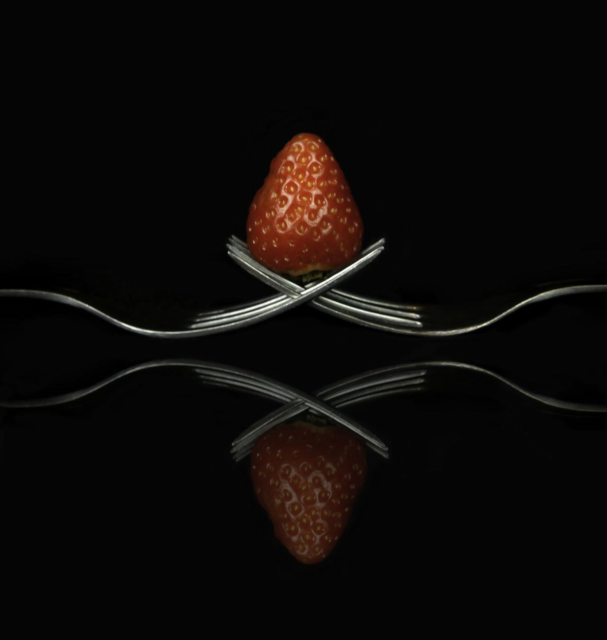 Strawberry on two forks against black
