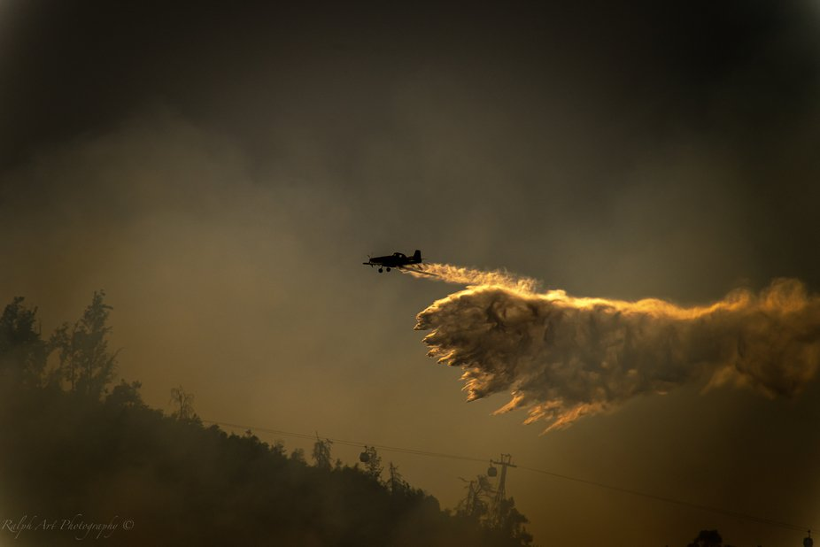 A plane flying over the hill and dropping it's load to fight the fire