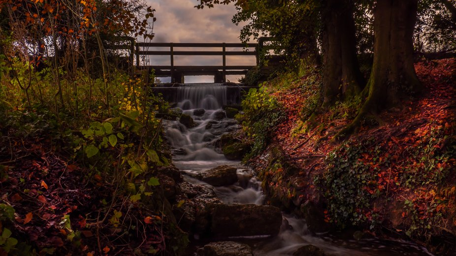 Long exposure shot of Waterfall forming the outfall from Stanton Country Park Lake in autumn.