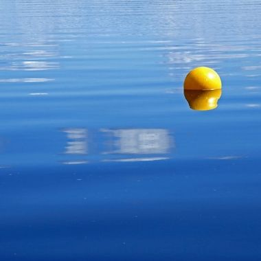 A yellow buoy on a calm river.