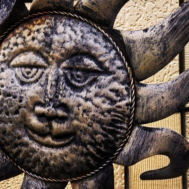 A close-up of a metal sun ornament.