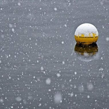 A yellow boy on a calm river on a snowy morning.