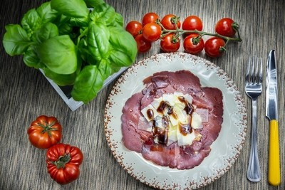 Italian bresaola with parmesan cheese and some drops of balsamic vinegar. It is a typical, tasty and tasty appetizer.