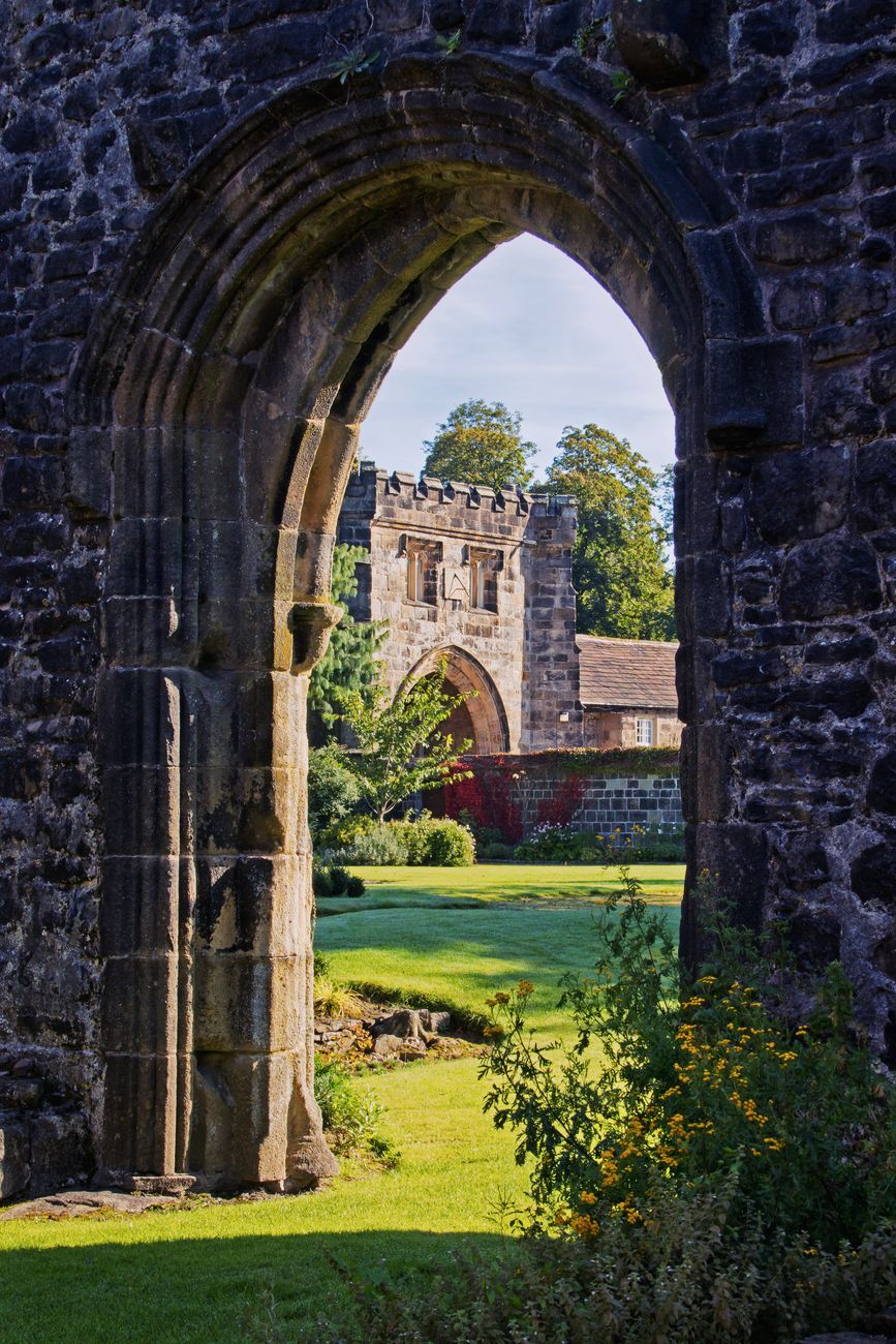The imposing historic architecture of Whalley Abbey, viewed through an arch