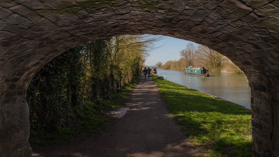 Walkers on the Tow path of the Kennett & Avon Canal below Caen Hill following a narrowboa...
