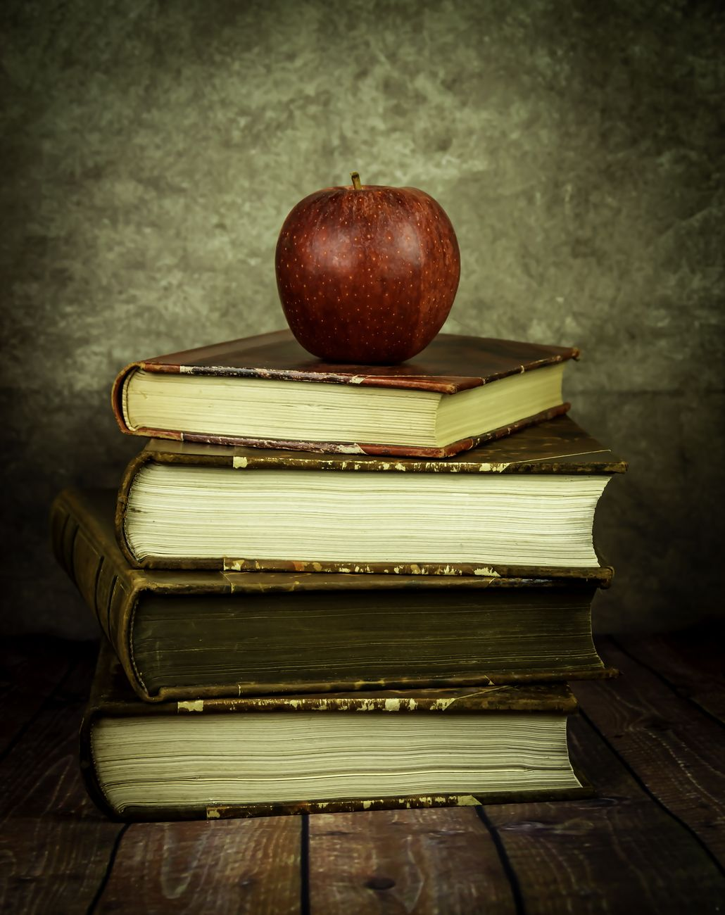 Still life pile of books and apple