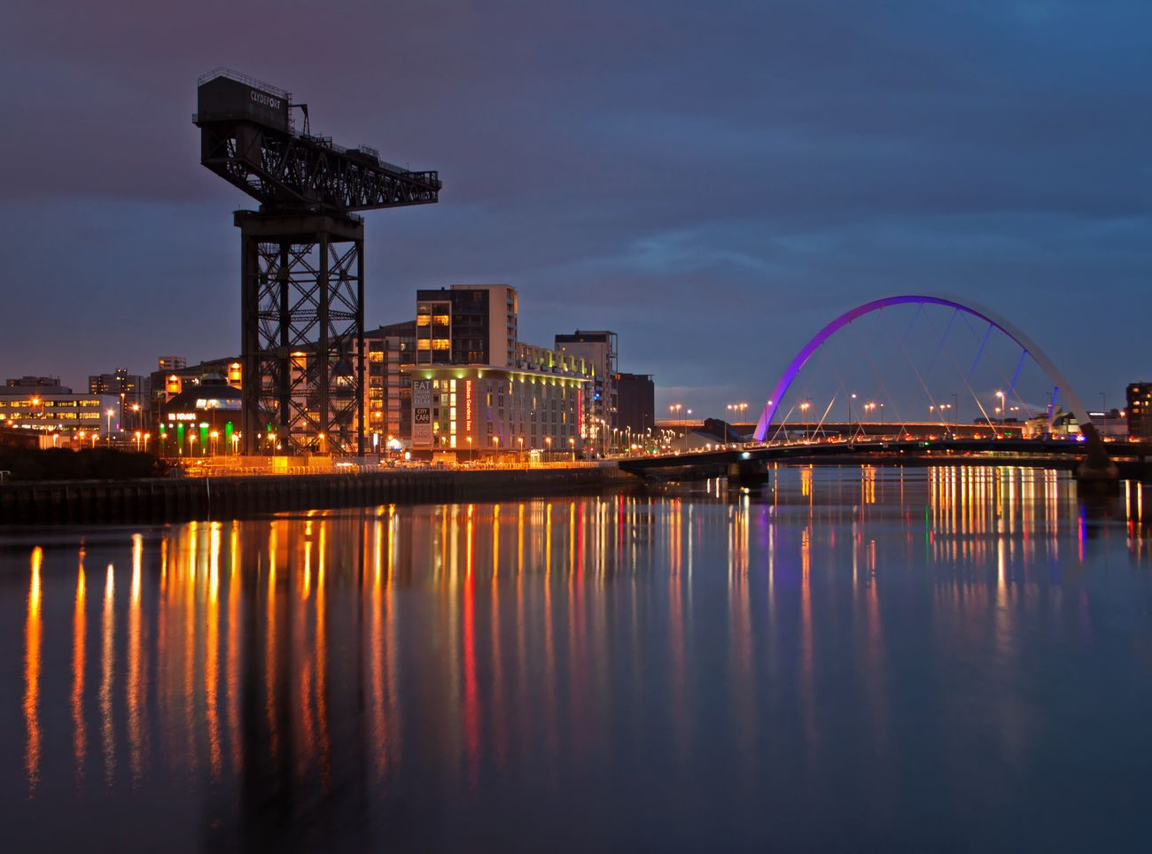 The gentrified section of the River Clyde, with just one remaining crane from the old shipyards. Viewed after dark