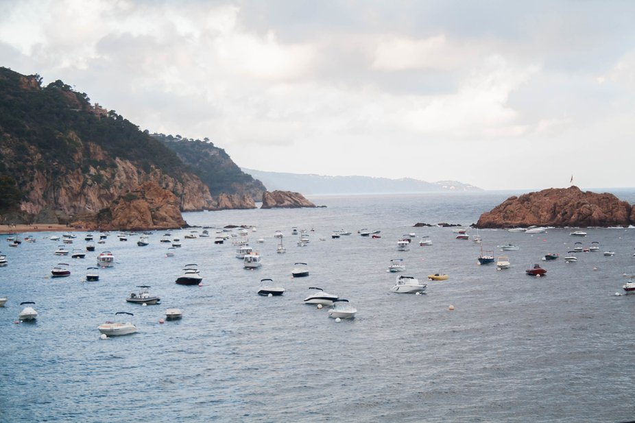 water surrounded by rocks with boats
