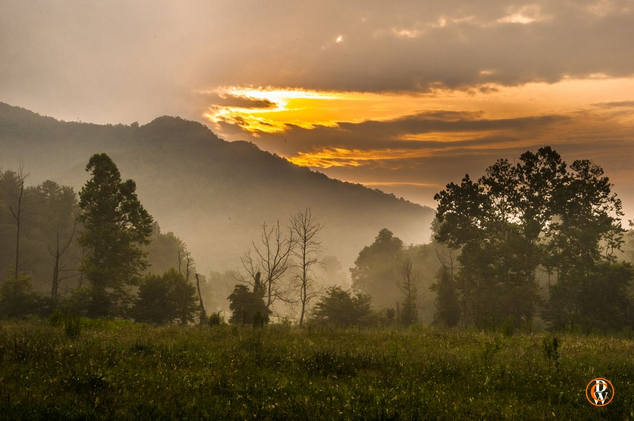 The sun breaks the morning fog as it comes over the top of the great smoky mountains national par...