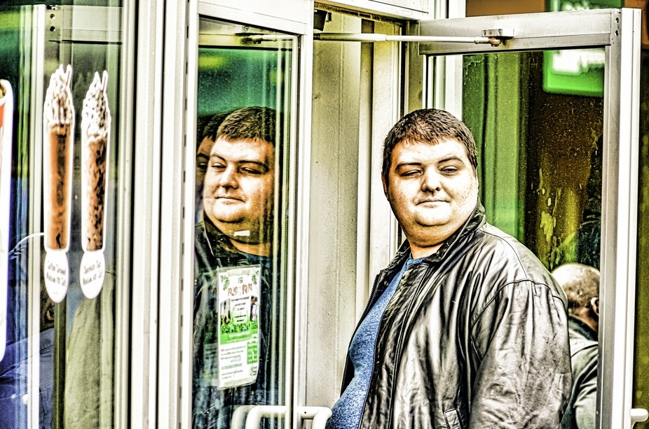 Half-awake guy standing by  mirror.