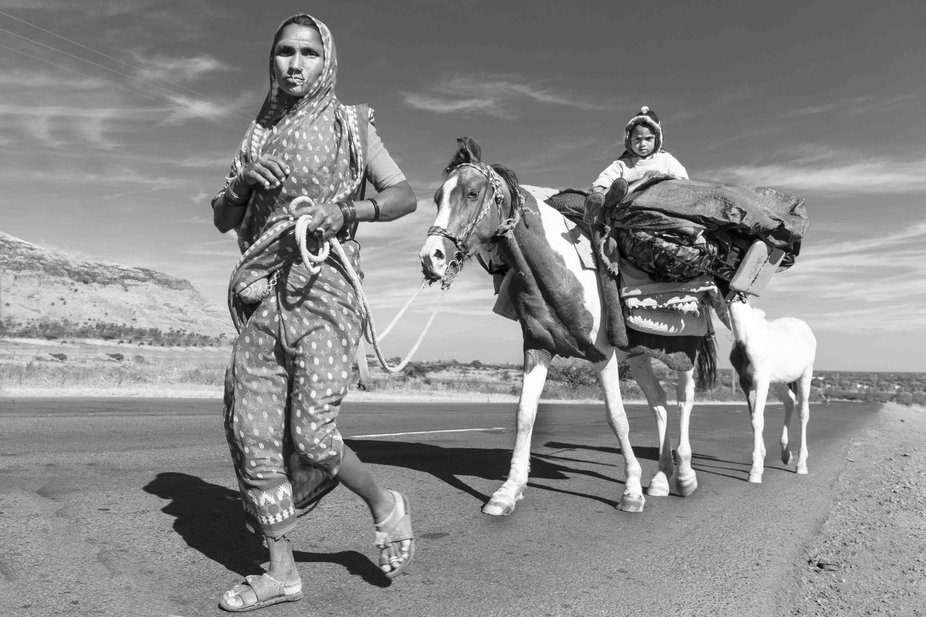 A nomadic tribal family on the move in a rural location in western India.