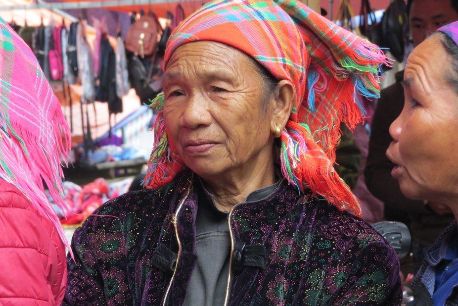 Taken in one of the remote village marketplaces of Sapa, Vietnam, the women wear colourful headpi...