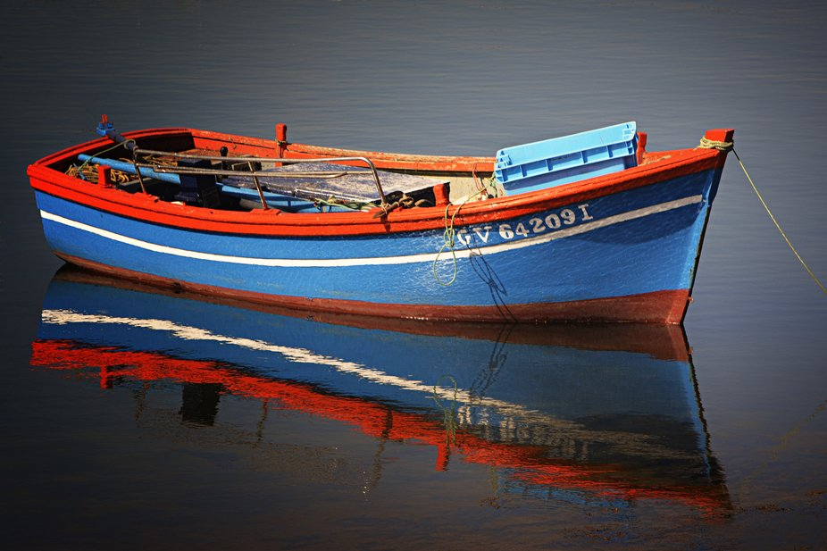 A colorful rowboat in a Brittany harbor