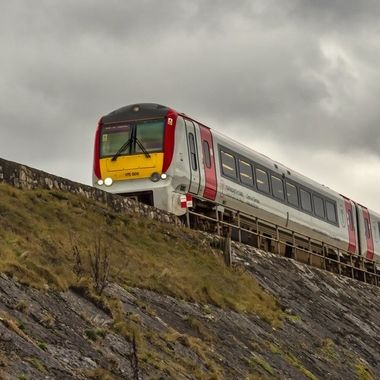 A train on top of an embankment.