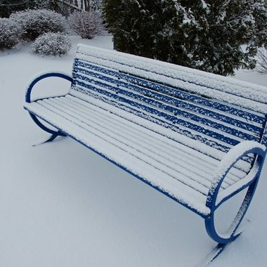 A snow-covered park bench.