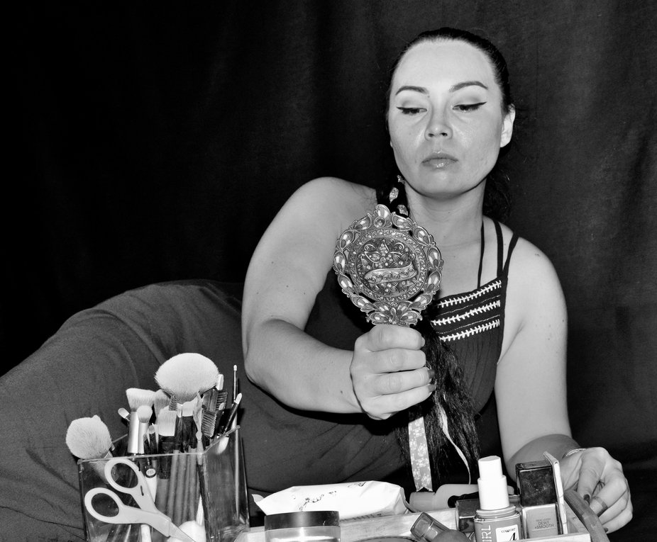 With elegant tools and manner she paints her face for herself.
