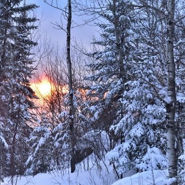 Sunset on a cloudy evening over a snowy ridge