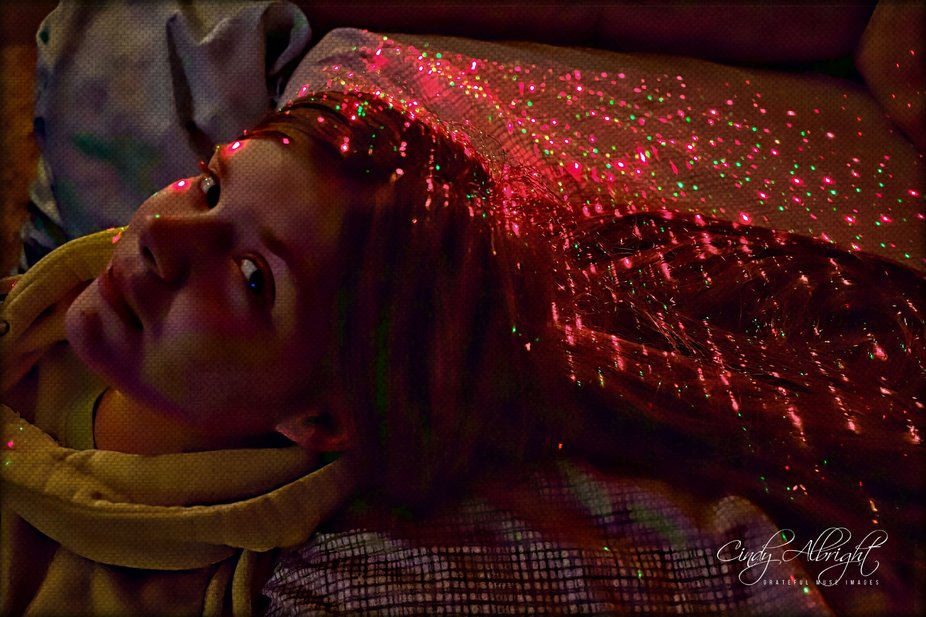 I call this the Night Before 12, because it is the last day my Granddaughter was 11 years old.  I saw the laser lights on her hair, and I just had to take this photo!