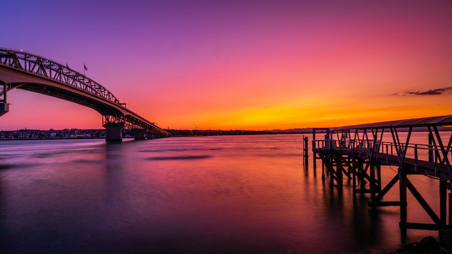 A long exposure shot of an Auckland, New Zealand summer sunset with the iconic Harbour Bridge and...