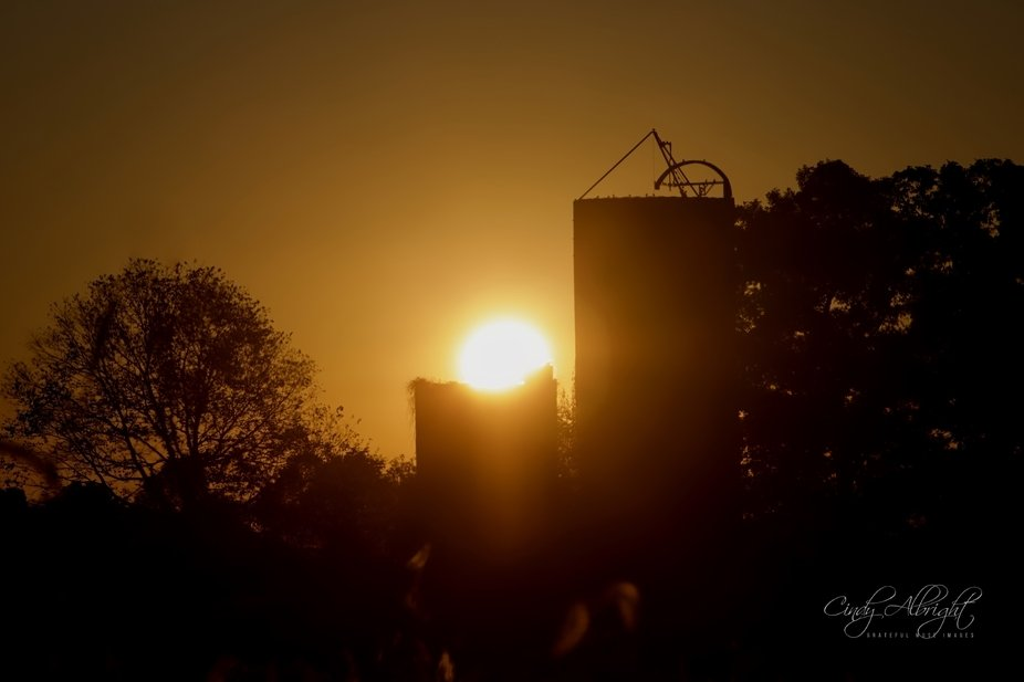 An October morning sunrise above a silo made me think of a giant candle.