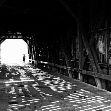 A person standing at the entrance of an old covered bridge.