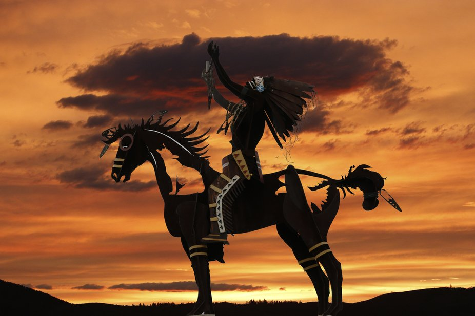 Carving of Indian on horse against brilliant sunset