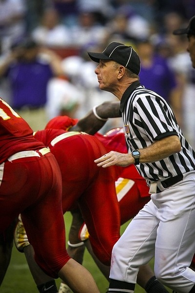 Football umpire observing action in offensive backfield