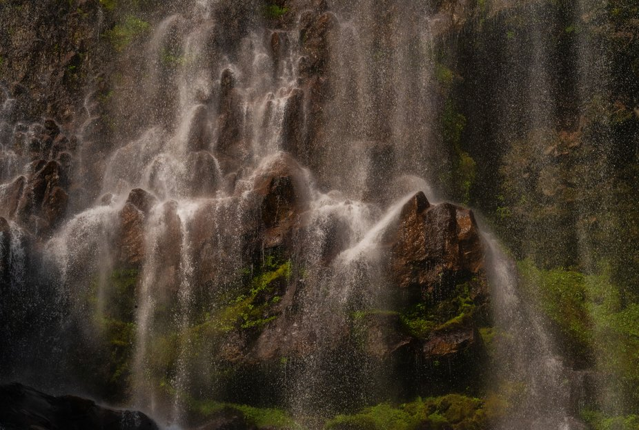 Water droplets drape over rock formations at the edge of Spray Falls on the northern face of Mt R...