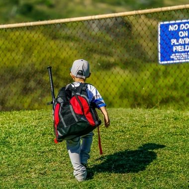 Five year old off to baseball practice with a back pack full of all the essentials, bat, ball, glove and snacks!