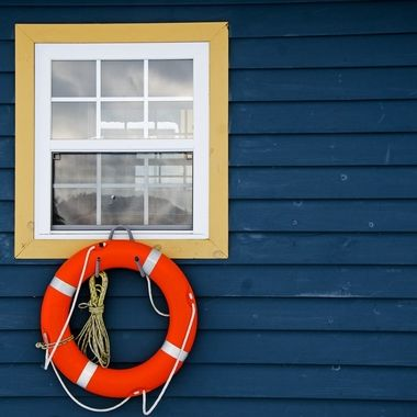 A life preserver hanging below an exterior window.