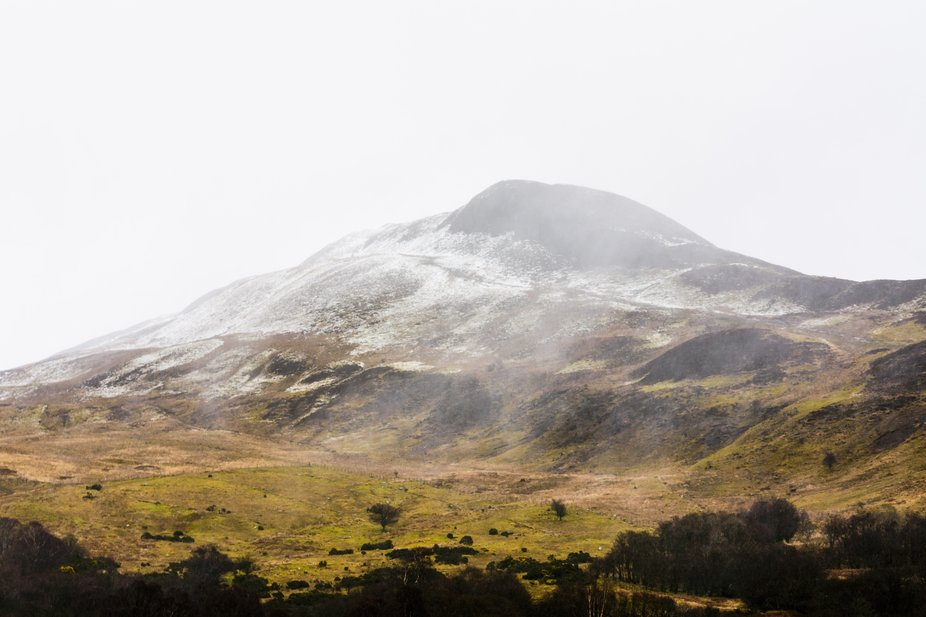 A landscape photo of a partially snow-covered mountain with fog descending upon it. It was shot c...