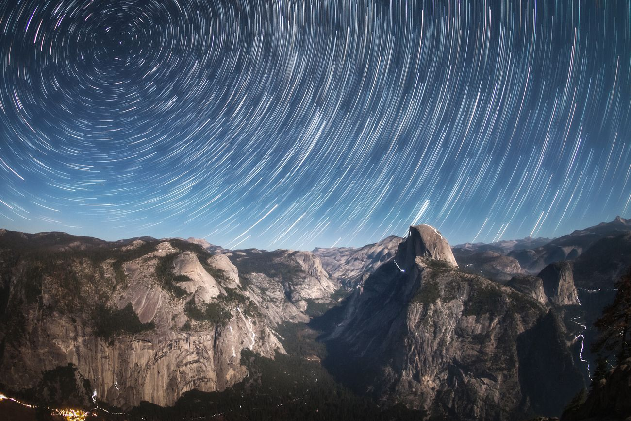 Startrails above Yosemite Valley and lighttrails of climbers at the rocks.