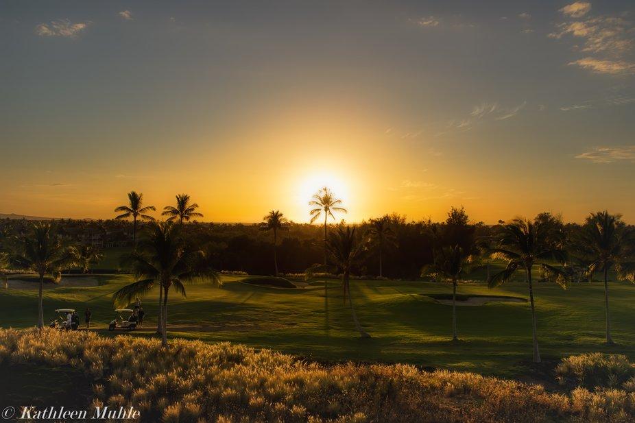 As the sun sets on the Kona Coast of Hawaii, the golfers play till the ray of light.