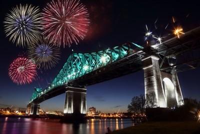 Colorful fireworks explode over bridge.